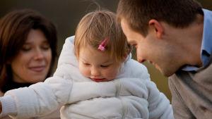 mor och far som tittar kärleksfullt på sitt lilla barn
