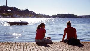 Unga människor sitter vid en kaj, i bakgrunden en båt.