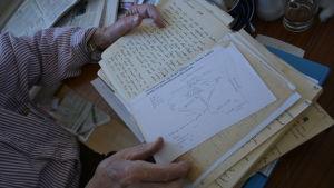Händer tillhörande en äldre person håller i en gammal dagbok.