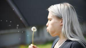 Petra Olli blåser på en torkad smörblomma.