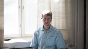 En man sitter på en stol framför ett fönster. Han har en blå skjorta på sig. Han ser in i kameran.