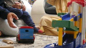 Familjen sitter på golvet bakom barnets leksaker.