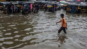 En man går genom översvämmade gator i utkanten av Bombay.