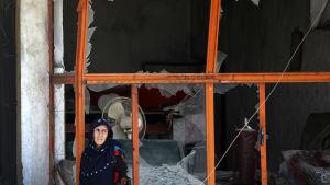 En afghansk kvinna står framför en söndrigt fönster efter en bombattack i västra Kabul.