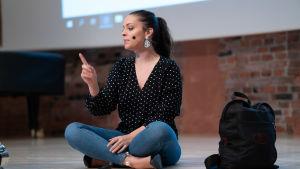 Felicia Margineanu sitter på scengolvet med benen i kors under en föreläsning om unga och självkänsla.