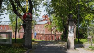 Portti, jonka takana suuri punatiilinen rakennus.