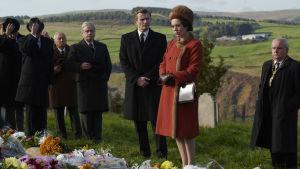 Storbritanniens drottning klädd i en röd kappa står på en begravningsplats i ett naturskönt landskap omgiven av svartklädda män.