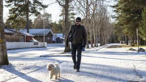 Auvo Heinoja happiviiksineen lenkittämässä koiraa.