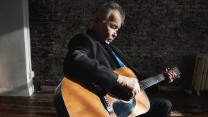 Countrymusikern John Prine spelar gitarr, profilbild