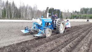 Ruslan Klymyk kör en traktor som sätter potatis på en åker i Ingå.