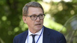 Finansminister Matti Vanhanen blickar snett i kameran med öppen mun. Han står framför gröna buskar och har slips och kostym på sig.