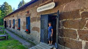 En kvinna står i dörröppningen till ett lågt stenhus.