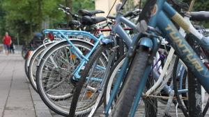 En rad av cyklar parkerade längs en gata.