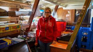 En kvinna står bakom en kassaapparat inne framför hyllor med varor.