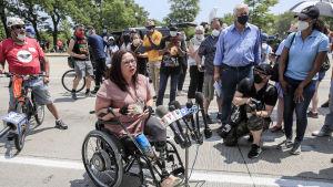 Tammy Duckworth sitter i rullstol mitt i en folkhop och håller tal.