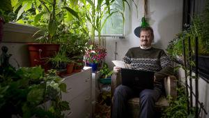 Veli Pekka Toropainen sitter ute på balkongen med sin laptop. Omkring sig har han massor med gröna växter och blommor.