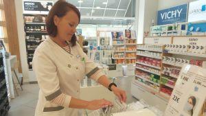 Farmaceut vid hylla för munskydd på apotek.