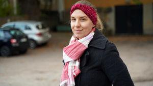 En kvinna med rött pannband, röd-vit halsduk och svart jacka står på en innergård där det finns bilar parkerade. Porträttbild.
