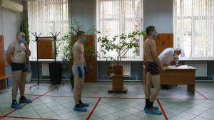Ryska värnpliktiga köar för hälsokontroll.