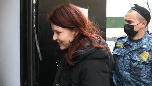 Rödhårig kvinna påväg in till en domstol. Bakom henne står en polis.