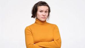 Misstänksam ung kvinna med armarna i kors