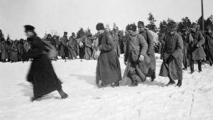 Svartvit bild från mars 1921. Människor i vinterkläder går i snön. Flyktingar kommer till Björkö