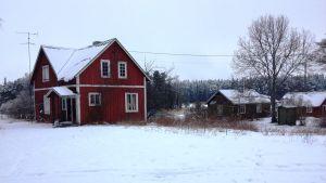 Rött hus i skärgården på vintern.