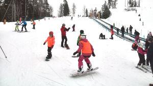 Barn åker snowboard.