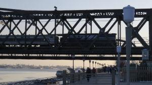 Tåg passerar gränsen mellan Nordkorea och Kina på en bro över floden Yalu i staden Dandong.