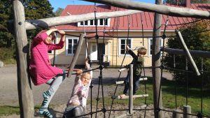 Barn klättrar i klätterställning på skolgården