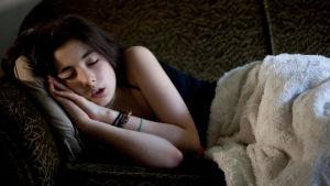 En flicka sover på en soffa.