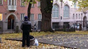En man, antagligen papperslös, står med ryggen mot, utanför kyrkan.