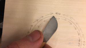 Dubbla rader med pilar i en cirkel, skissade i blyerts på en ljus träskiva och en hand som håller en kniv med kort egg, som används för karvsnitt.