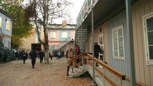 En gård med trähus och mycket folk, främst barn
