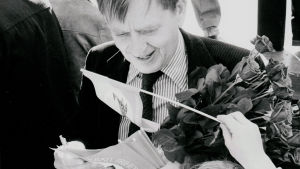Svartvit bild av Olof Palme med en bukett rosor och kampanjvimpel.
