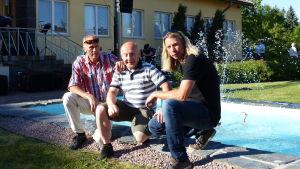 tre män sitter på huk framför en fontän. Männen är sommarklädda. Runt den lilla fontänen finns gräs och buskar.