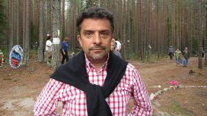 Aleksandr Arkangelskij, en mrkårig medelålders man med skägg och röd-vit-rutig skjorta stirrar stint in i kameran med skog och människor i bakgrunden.