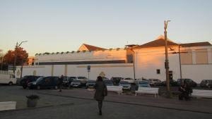 En vit fängelsebyggnad med en parkeringsplats i förgrudnen.