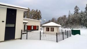 Vit byggnad med mörgrå detaljer intill en inhägnad. Innaför staketet ett vitt litet hus. I bakgrunden skog.
