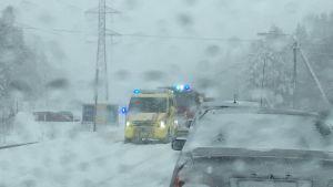 Ambulans och brandbil syns genom en snöig vindruta. Trafikolycka på Myrgrundsvägen i Vasa.