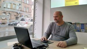 En man sitter framför en dator vid ett skyltfönster.
