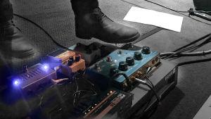 Fot som trycker på effektpedaler för elgitarr på pastis konsert 2019.