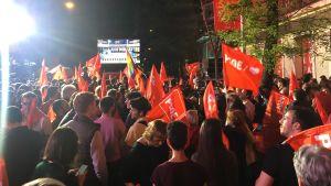 Anhängare till Spanska socialistiska arbetarpartiet firar utanför partikontoret i Madrid.