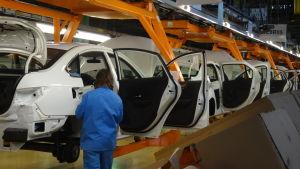Fabriksarbetare står vid en rad vita halvfärdiga bilar.