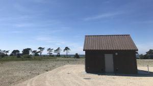 Liten byggnad med pumpstation intill stranden.