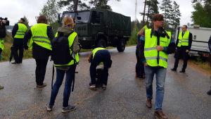 Flera personer i gula västar på en asfalterad väg. I bakgrunden ett militärfordon och några andra bilar.