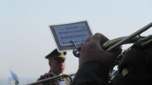 Ett blåsinstrument och noter. En soldatdirigent i bakgrunden.