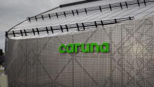 En stålbyggnad med Carunas gröna logotyp.