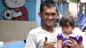 Pappa med barn i famnen i ett slumområde i Malang, Indonesien
