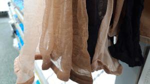 Sukkahousunäytteitä roikkumassa kaupan sukkaosastolla.